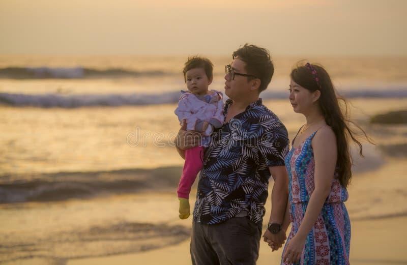 Pares coreanos asiáticos felizes e bonitos novos que guardam a filha do bebê que anda na praia do por do sol que aprecia junto o  fotografia de stock royalty free