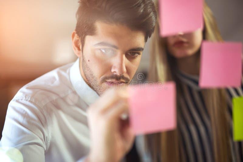 Pares creativos felices de los hombres de negocios que escriben en etiquetas engomadas imagen de archivo