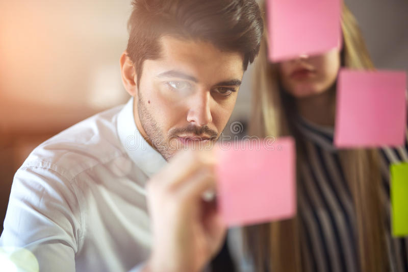 Pares criativos felizes de executivos que escrevem em etiquetas imagem de stock