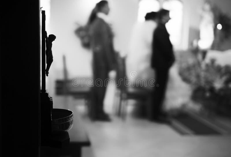 Pares cristianos de la boda en la iglesia católica Foco en el statu de Jesús fotos de archivo