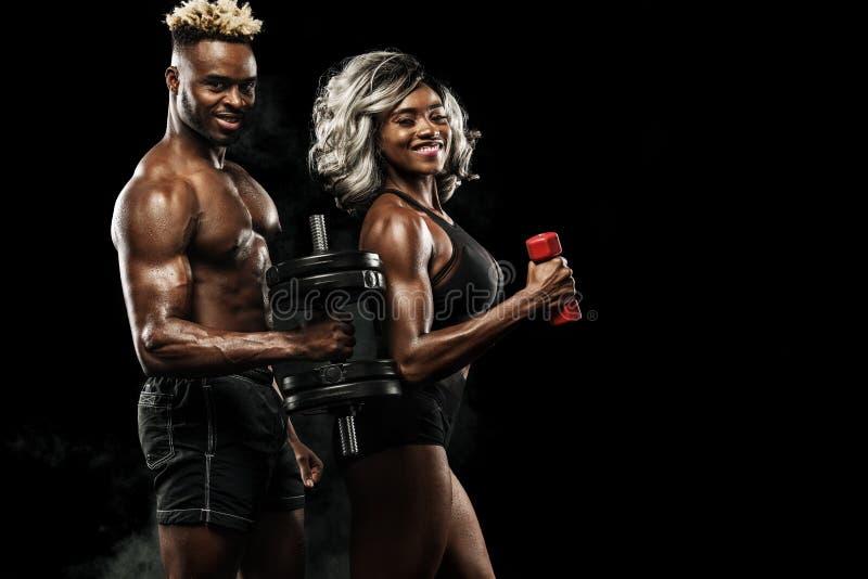 Pares da aptidão de atletas que levantam no fundo preto, cuidado saudável do corpo do estilo de vida Conceito do esporte com espa imagens de stock