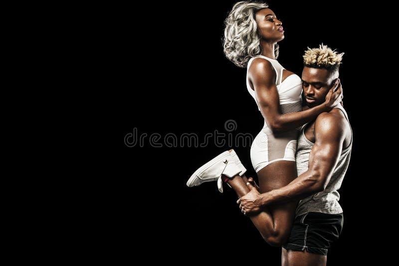 Pares da aptidão de atletas que levantam no fundo preto, cuidado saudável do corpo do estilo de vida Conceito do esporte com espa imagens de stock royalty free