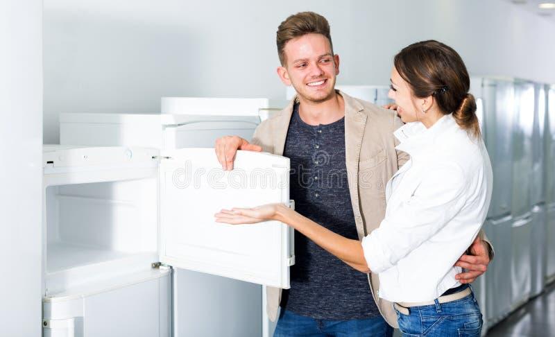 Pares da família de classe média que escolhem o refrigerador novo fotos de stock