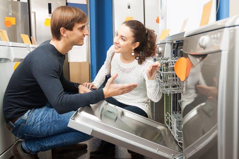 Pares da família que olham máquinas de lavar louça imagens de stock