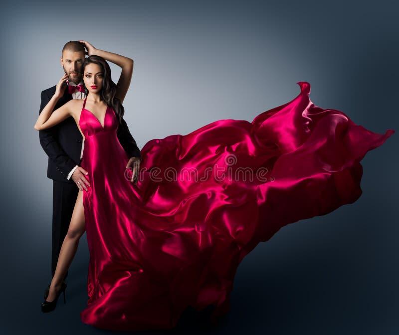 Pares da forma, mulher bonita nova no vestido de ondulação de voo da beleza, homem elegante fotografia de stock royalty free