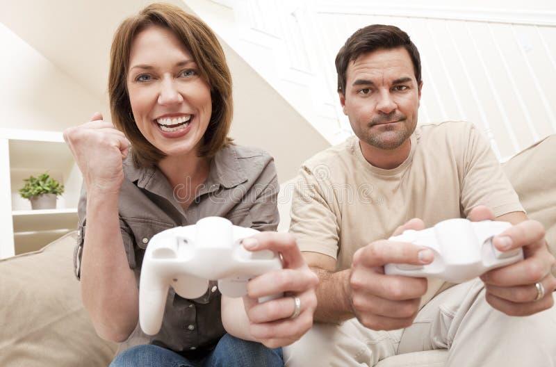 Pares da mulher do homem que jogam o jogo video do console imagem de stock
