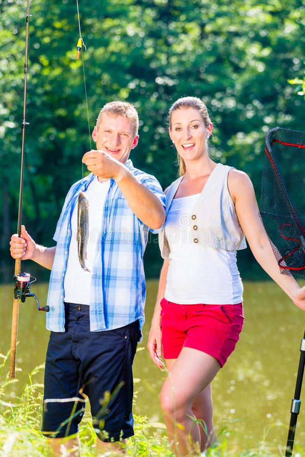 Pares da pesca, homem e mulher, no lago que é orgulhoso da captura foto de stock