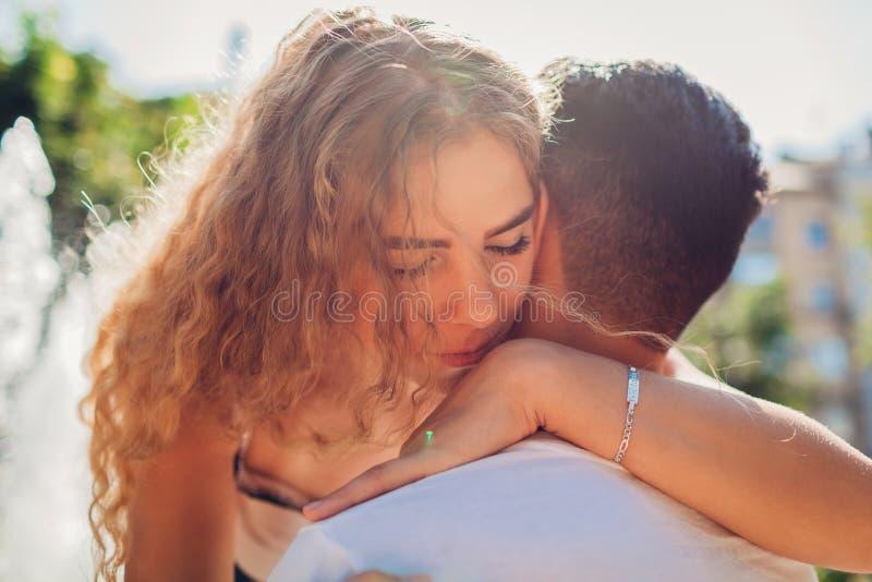 Pares da raça misturada no amor que abraça fora Homem árabe e mulher branca que andam na cidade pela fonte imagens de stock royalty free