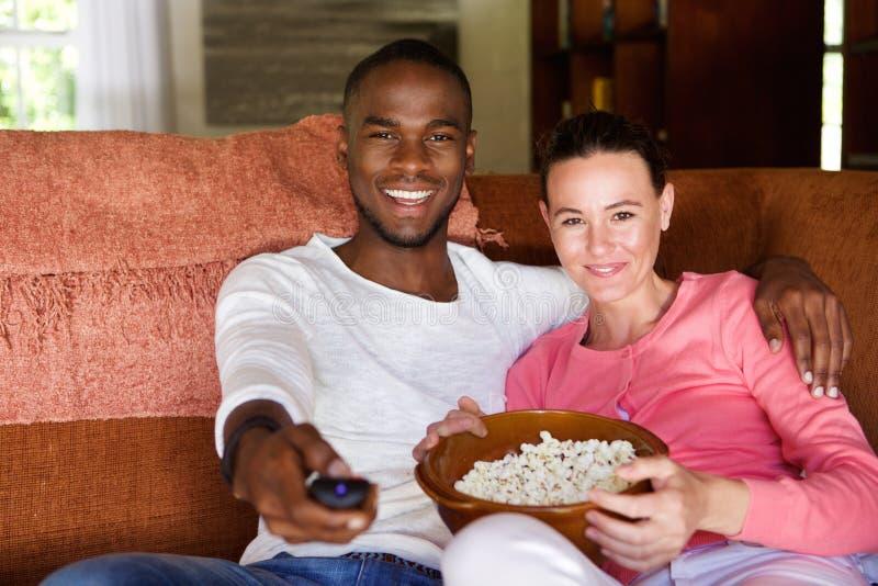 Pares da raça misturada que olham um filme em casa fotografia de stock royalty free