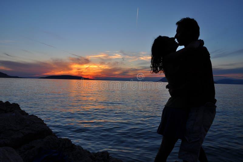 Pares da silhueta que beijam sobre o fundo do por do sol do mar foto de stock royalty free
