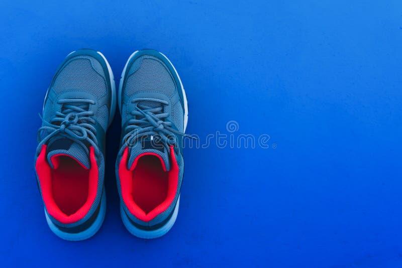 Pares da vista superior de sapatas de corrida azuis e vermelhas do esporte isoladas em escuro - fundo azul com espaço da cópia Es fotografia de stock royalty free