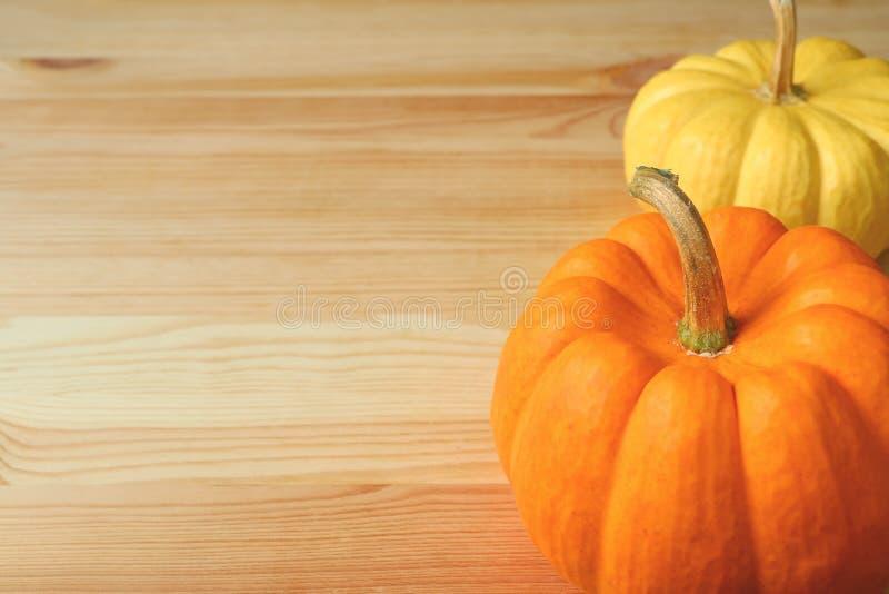 Pares de abóboras maduras brilhantes da cor amarela e alaranjada com a haste na luz - tabela de madeira marrom, com espaço livre  imagens de stock royalty free