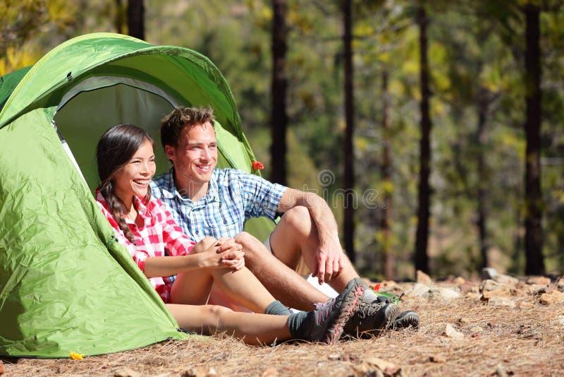 Pares de acampamento na barraca que senta-se olhando a vista imagens de stock