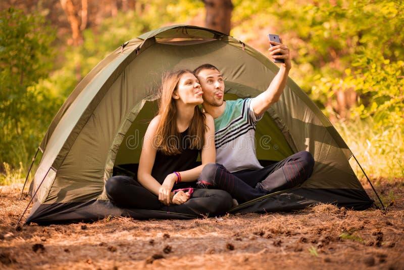 Pares de acampamento na barraca que toma o selfie Amigos felizes que t?m o togheter do divertimento Povos do conceito imagem de stock