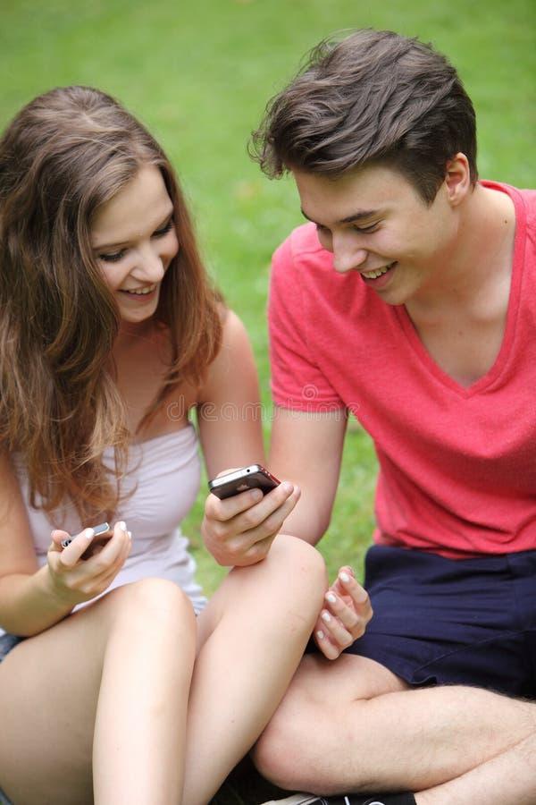 Pares de adolescentes que olham seus telemóveis fotos de stock royalty free