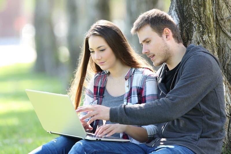 Pares de adolescentes que procuram satisfeitos em linha em um portátil fotografia de stock royalty free