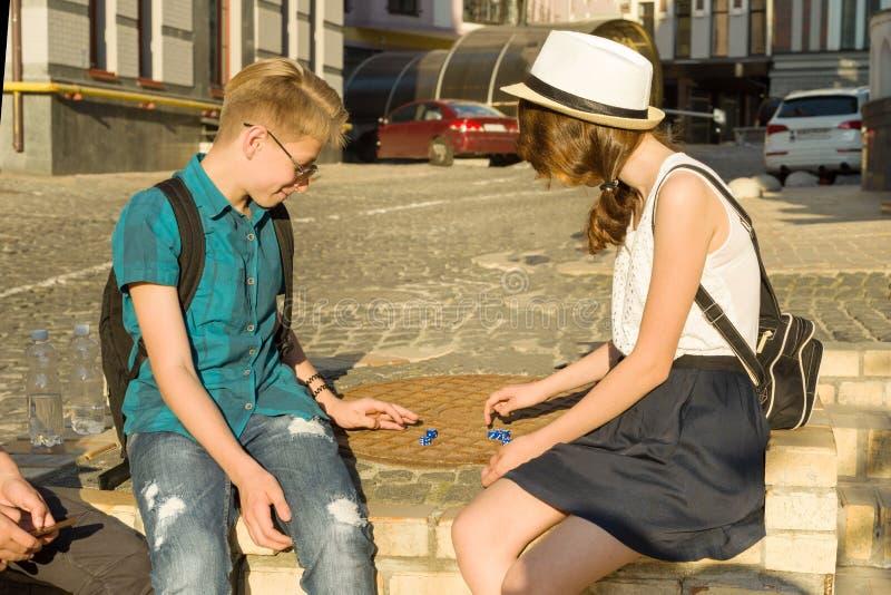 Pares de adolescentes que relaxam e que jogam um dado de jogo do jogo de mesa, fundo da rua da cidade fotografia de stock royalty free