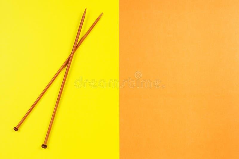 Pares de agulhas de confecção de malhas de madeira no fundo amarelo e alaranjado fotografia de stock