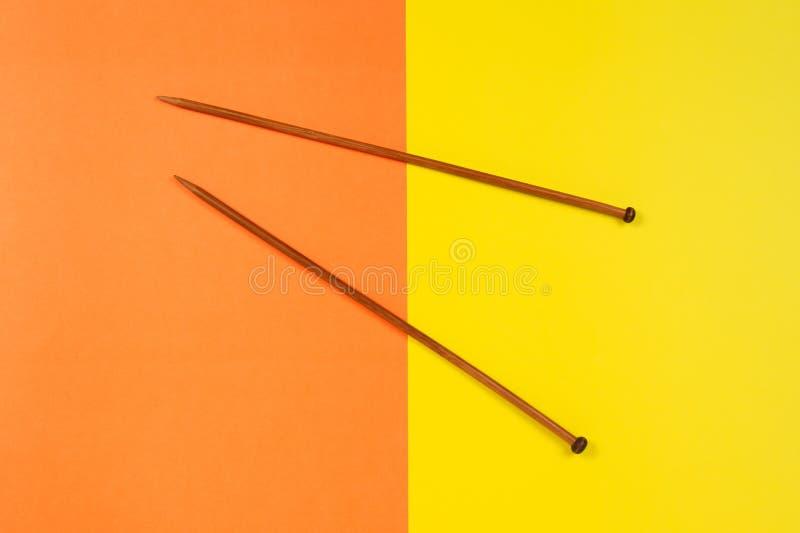 Pares de agulhas de confecção de malhas de madeira no fundo amarelo e alaranjado foto de stock royalty free