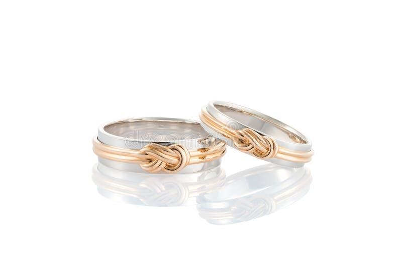 Pares de alianças de casamento do ouro branco com o nó cor-de-rosa do ouro isolado sobre fotografia de stock royalty free