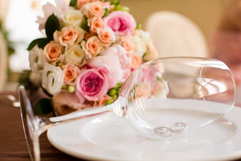 Pares de alianças de casamento em um vidro de vinho fotografia de stock royalty free