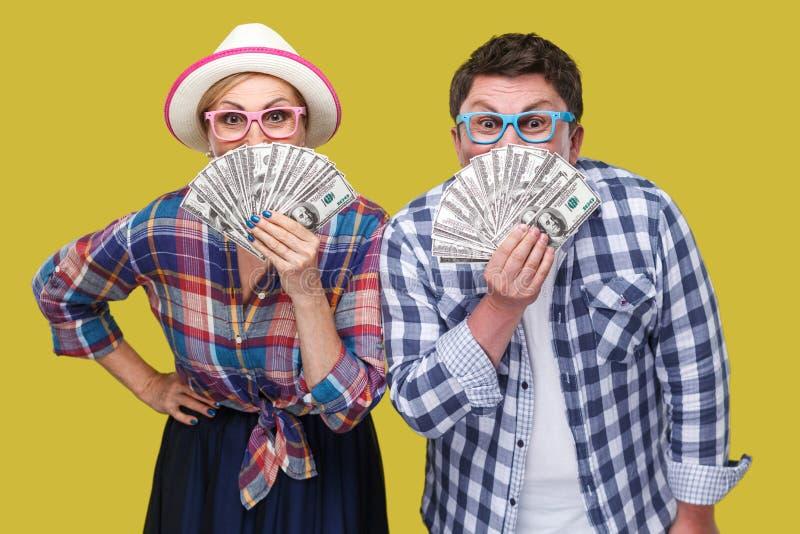 Pares de amigos divertidos, del hombre adulto y de la mujer en la camisa a cuadros casual que coloca junto sostenerse, cubriendo  fotografía de archivo