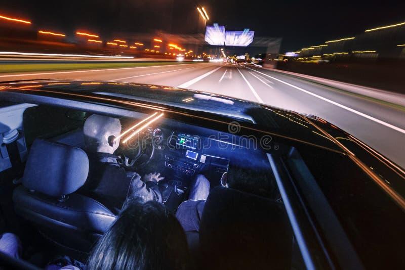 Pares de amigos em uma condução de carro luxuosa na noite fotos de stock