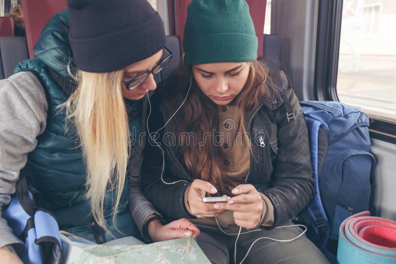 Pares de amigos fêmeas que olham o smartphone quando no trem imagem de stock royalty free