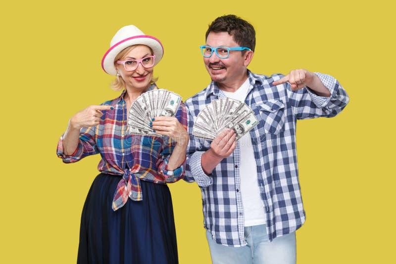 Pares de amigos ricos, del hombre adulto y de la mujer en la camisa a cuadros casual que se coloca junto que sostiene la fan de d fotos de archivo libres de regalías