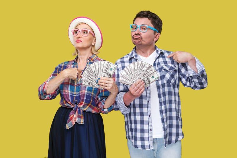 Pares de amigos seguros, de homem adulto e de mulher na camisa quadriculado ocasional que está unido mantendo o fã dos dólares e  imagem de stock