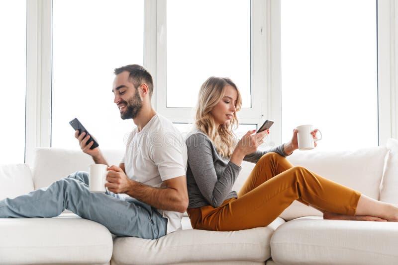 Pares de amor bonitos dentro que usam em casa telefones celulares foto de stock
