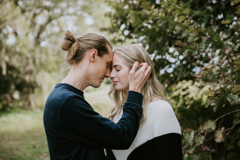 Pares de amor bonitos românticos bonitos novos que olham cara a cara em cada outro os olhos exteriores na natureza imagens de stock