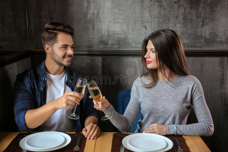 Pares de amor com vidros do champanhe no restaurante na data romântica foto de stock