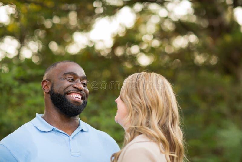 Pares de amor da raça misturada que abraçam e riso fotografia de stock royalty free