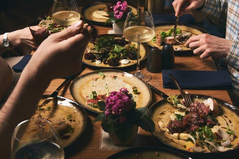 Pares de amor felizes que apreciam o jantar, sentando-se na tabela e no vinho da bebida imagem de stock royalty free