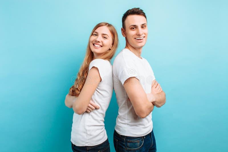 Pares de amor, homem e mulher, vestidos nos t-shirt brancos, lado a lado e sorrindo, contra um fundo azul imagem de stock royalty free