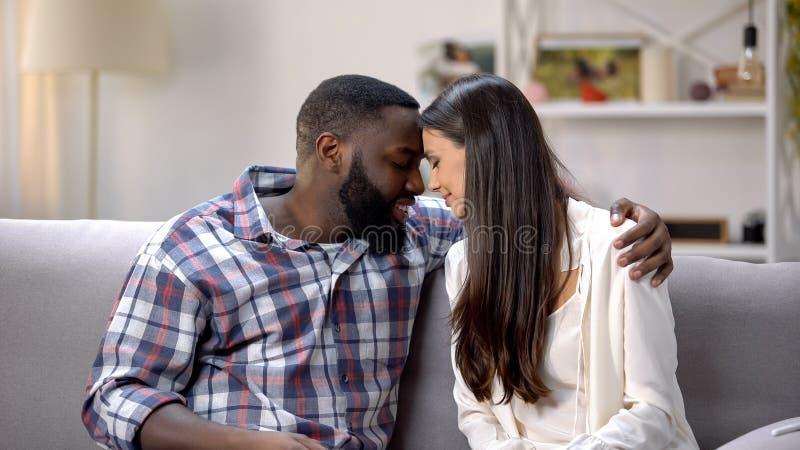 Pares de amor de la raza mixta que tocan las frentes y que abrazan en el sofá, dulzura imagen de archivo