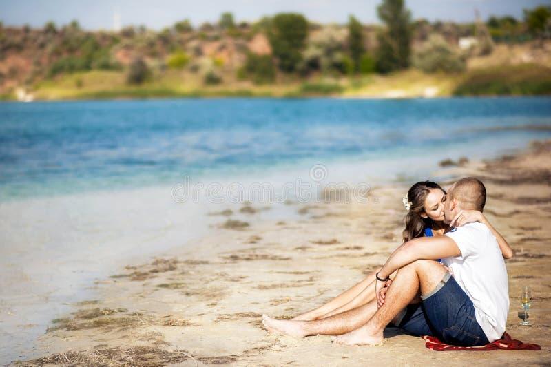 Pares de amor na costa o beijo do lago, mar na areia Piquenique do verão dos amantes com champanhe Beijo contra a água fotografia de stock royalty free