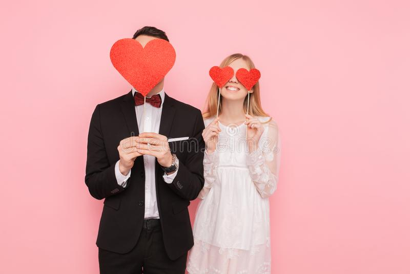 Pares de amor no amor, no homem e na mulher com corações vermelhos em seus olhos, sobre o fundo cor-de-rosa Conceito do dia dos a fotos de stock royalty free