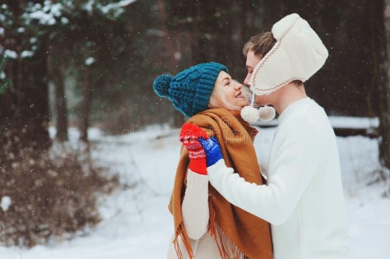 pares de amor novos felizes que andam na floresta nevado do inverno, coberta com a neve fotos de stock royalty free