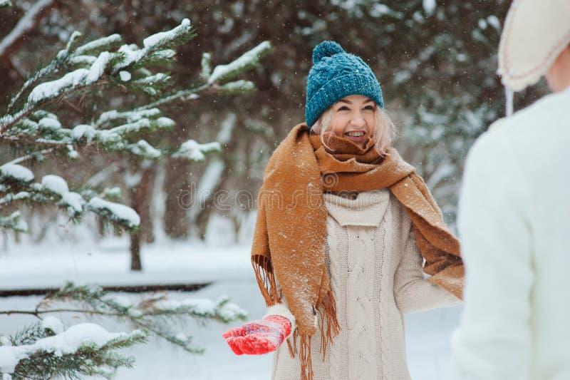 pares de amor novos felizes que andam na floresta nevado do inverno, coberta com a neve fotografia de stock