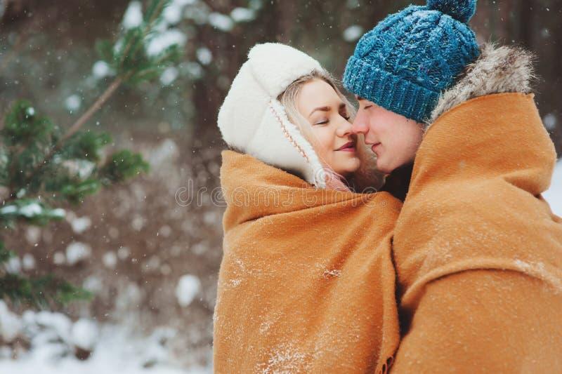 pares de amor novos felizes que andam na floresta nevado do inverno, coberta com a neve foto de stock