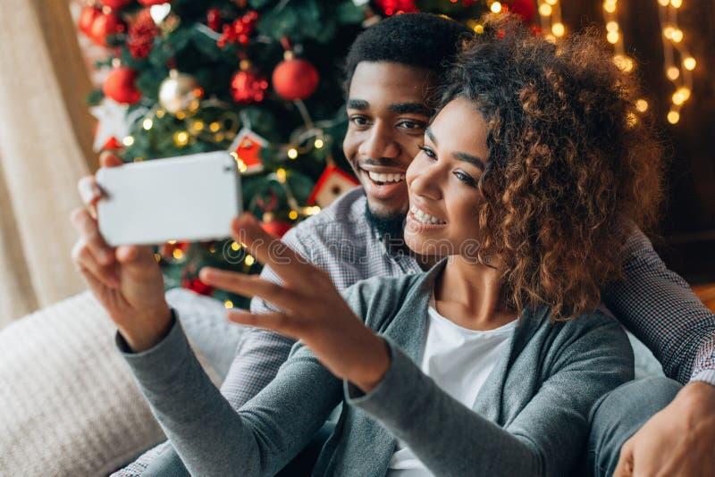 Pares de amor novos que fazem o selfie com árvore de Natal fotografia de stock royalty free