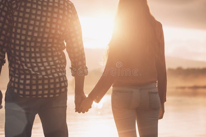 Pares de amor novos que guardam as mãos no por do sol fotografia de stock
