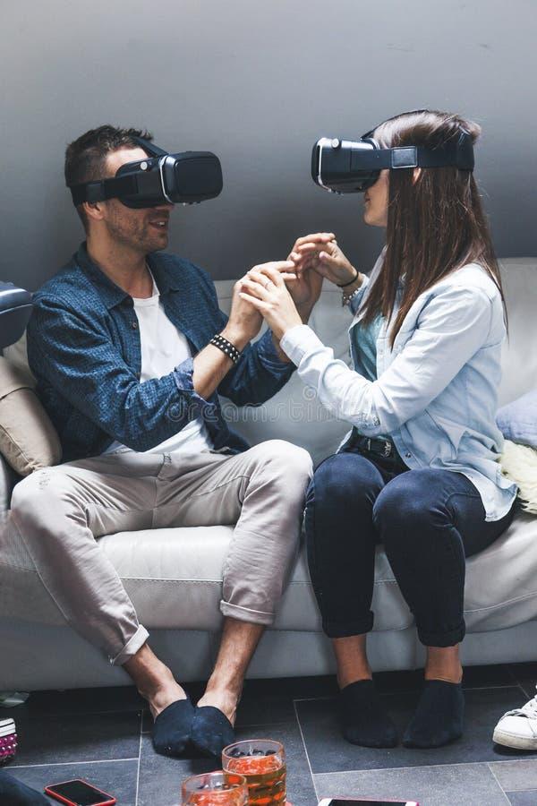 Pares de amor novos que jogam vidros da realidade virtual dos jogos de v?deo imagem de stock
