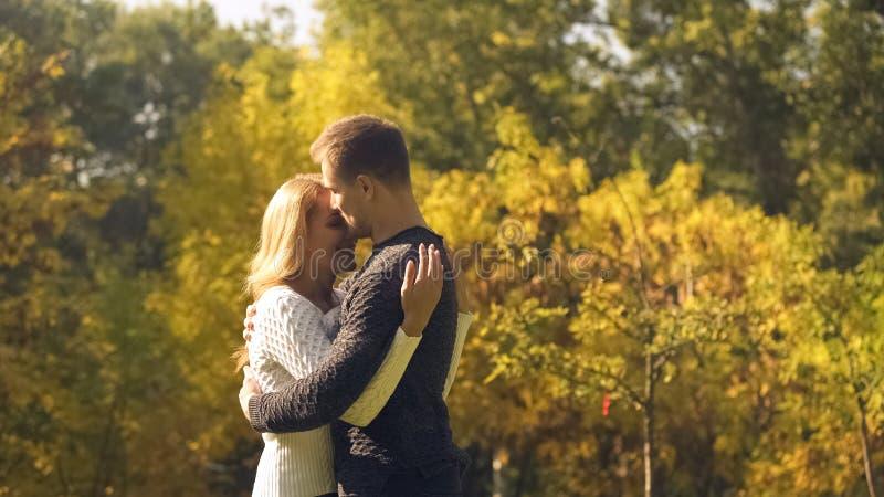 Pares de amor que abrazan en parque del otoño, amor a pesar de las dificultades, relaciones fotos de archivo