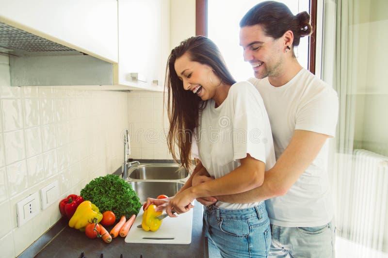 Pares de amor que cocinan en la cocina fotos de archivo