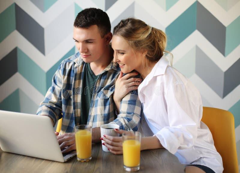 Pares de amor que desayunan mientras que se sienta en la tabla en una cocina en casa y la mirada del ordenador portátil fotos de archivo libres de regalías
