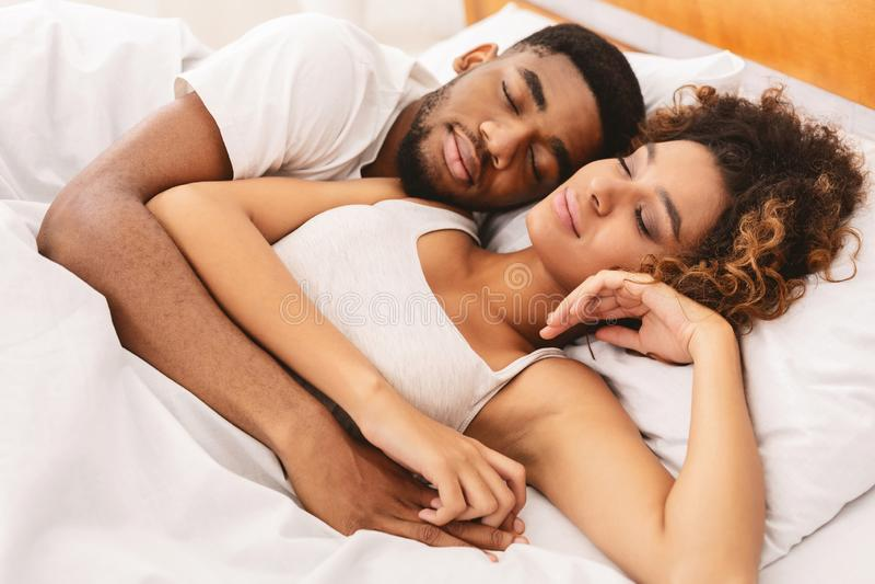 Pares de amor que dormem na cama e no aperto fotografia de stock