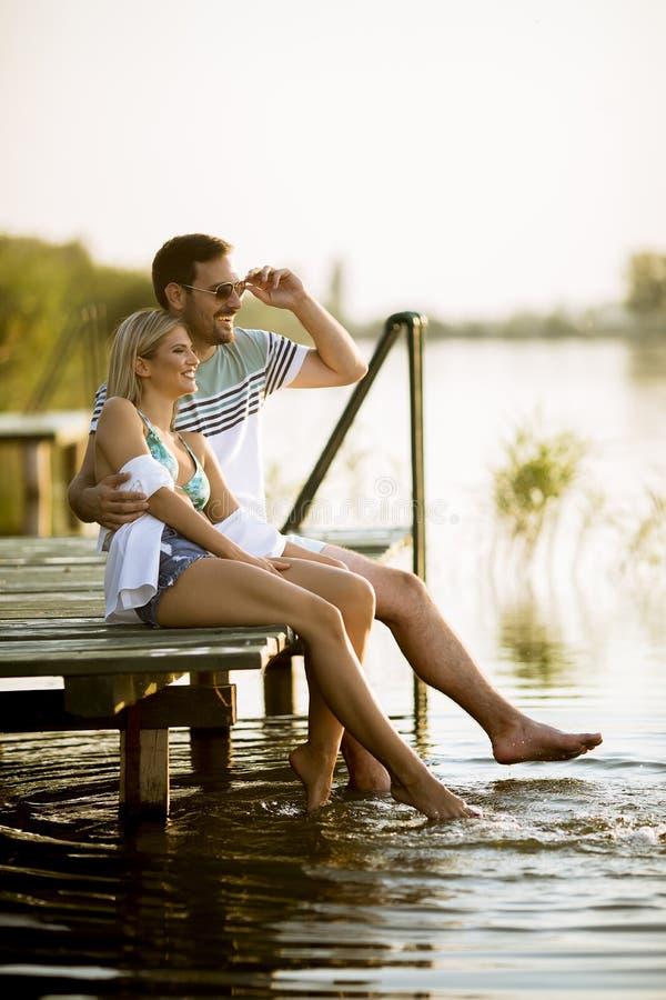 Pares de amor que se sientan en el embarcadero en el lago fotos de archivo